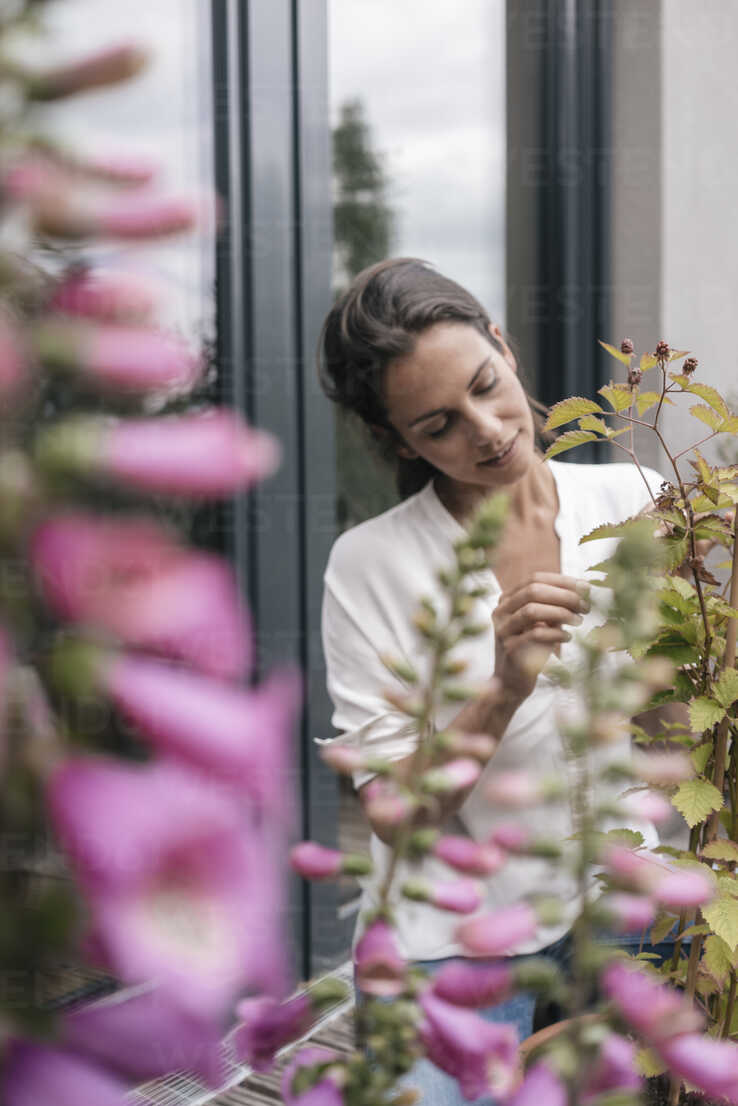 Woman caring for plant on balcony - JOSF01636 - Joseffson/Westend61