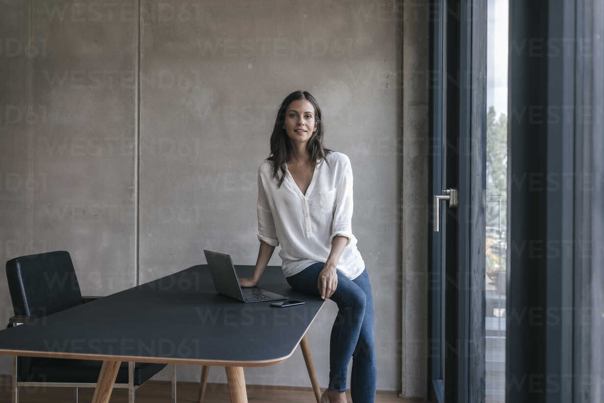 Portrait of smiling woman sitting on table with laptop and cell phone - JOSF01663 - Joseffson/Westend61