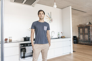 Young man standing in kitchen at home - JOSF01672