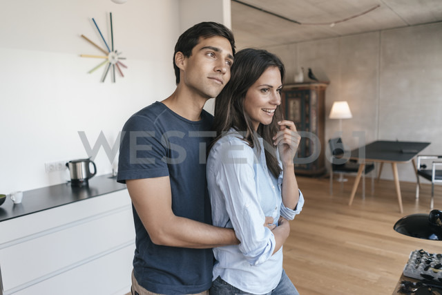 Happy couple hugging in kitchen at home - JOSF01675 - Joseffson/Westend61