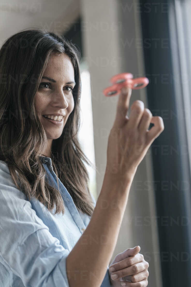Smiling woman playing with fidget spinner - JOSF01678 - Joseffson/Westend61