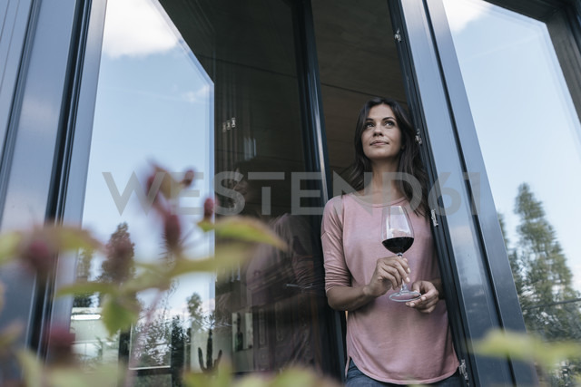 Woman holding glass of red wine looking out of window - JOSF01687 - Joseffson/Westend61
