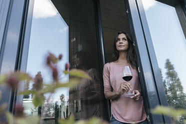 Woman holding glass of red wine looking out of window - JOSF01687