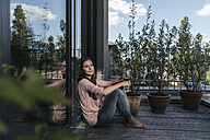 Woman with glass of red wine relaxing on balcony - JOSF01690