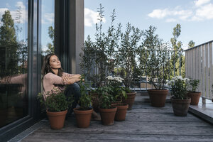 Woman relaxing on balcony surrounded by plants - JOSF01693