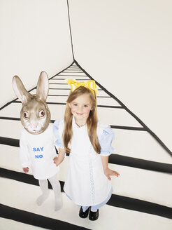 Portrait of smiling little girl dressed up as Alice in Wonderland hand in hand with girl with rabbit mask - FSF00955