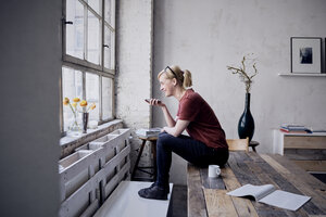 Woman sitting on desk in loft using cell phone - RBF05959