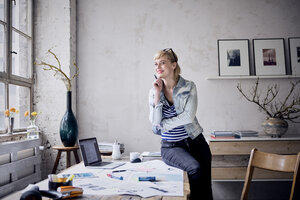 Portrait of smiling woman at desk in a loft - RBF05971