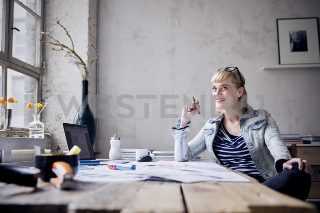 Portrait of laughing woman sitting at desk in a loft - RBF05974