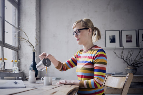 Woman pouring coffee in a mug at desk in a loft - RBF05980