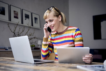 Portrait of smiling woman on the phone using laptop and tablet - RBF05986