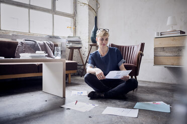 Smiling woman sitting on the floor in a loft looking at papers - RBF05992
