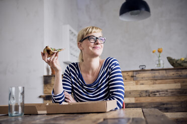 Portrait of smiling woman eating pizza - RBF05998