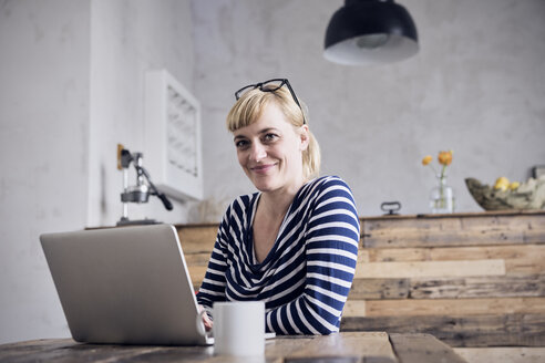 Portrait of smiling woman sitting at table with laptop and coffee mug - RBF06001