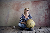 Smiling woman sitting on wooden floor in an unrenovated room with an old globe - RBF06016