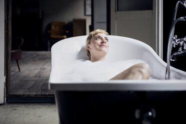 Portrait of happy woman taking bubble bath in a loft - RBF06019