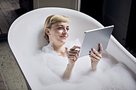 Portrait of relaxed woman taking bubble bath while using tablet - RBF06022
