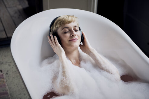 Blond woman taking bubble bath in a loft listenung music with headphones - RBF06025