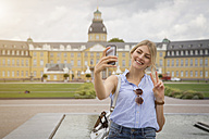 Germany, Karlsruhe, tourist taking selfie with smartphone - JUNF00900