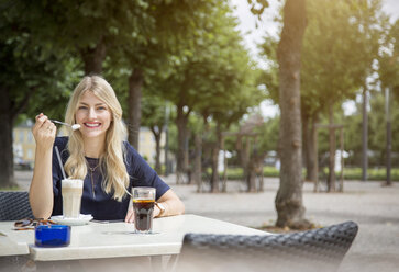 Portrait of laughing blond woman sitting at sidewalk cafe - JUNF00903