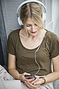 Relaxed young woman listening music with headphones and cell phone - JUNF00912
