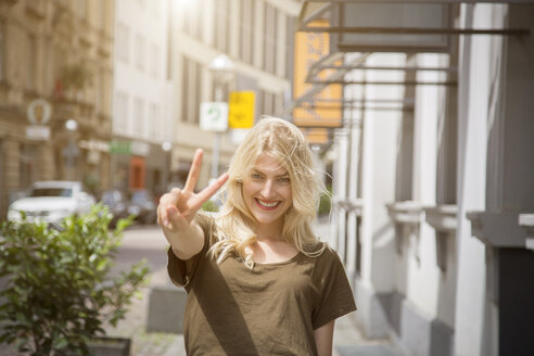Portrait of happy blond woman showing victory sign - JUNF00915