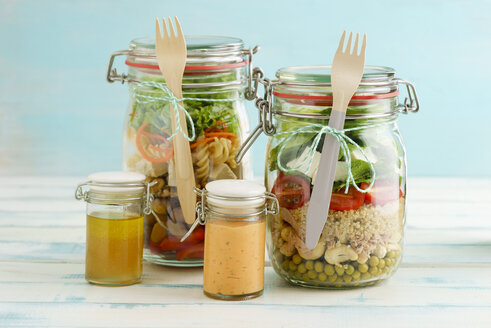 Preserving jars of mixed salads and jars of dressings - ECF01883