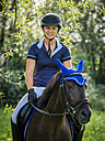 Smiling young woman horseriding on field - STSF01311