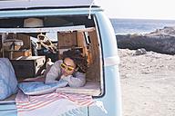 Spain, Tenerife, woman relaxing in van parked at seaside - SIPF01705