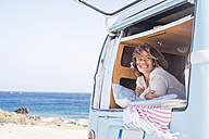 Spain, Tenerife, portrait of happy woman in van - SIPF01711