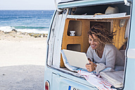 Spain, Tenerife, happy woman using laptop in van - SIPF01714