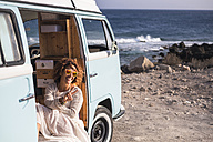 Spain, Tenerife, laughing woman sitting in van parked at seaside showing victory sign - SIPF01720