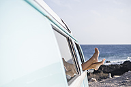Spain, Tenerife, legs of woman leaning out of car window - SIPF01723