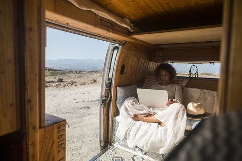 Spain, Tenerife, woman iusing laptop in van - SIPF01732