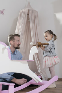 Father playing with toddler daughter in her nursery - SBOF00590