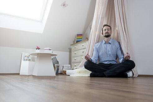 Father meditating in nursery - SBOF00596