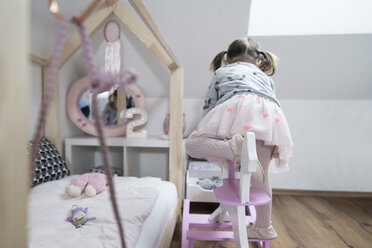 Toddler girl climbing on rocking horse in nursery - SBOF00599