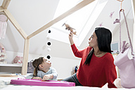 Mother and toddler daughter playing with toy plane in nursery - SBOF00605