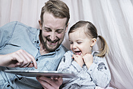 Father and his toddler daughter looking at tablet and laughing together - SBOF00608