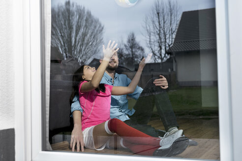 Girl in soccer outfit sitting next to father on floor in living room playing with soccer ball - SBOF00617