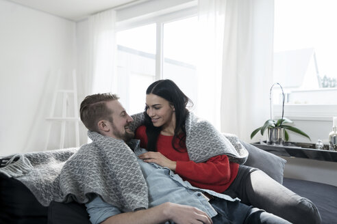 Couple cuddling under blanket on sofa in living room - SBOF00623