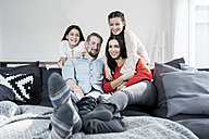 Family portrait of parents and twin daughters on sofa in living room - SBOF00629