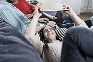 Girl with family lying on sofa holding tablet - SBOF00635