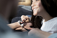 Daughter and father with smartwatch with mother waving - SBOF00638
