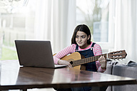 Girl playing guitar in front of laptop - SBOF00641