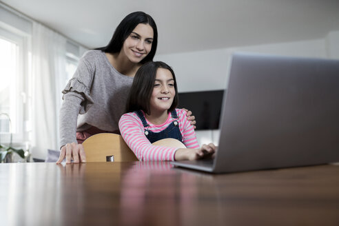 Mother and daughter smiling in front of laptop with daughter holding a guitar - SBOF00644