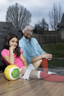 Girl in soccer outfit sitting next to father on floor in living room looking out window - SBOF00650
