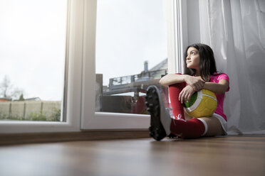 Girl in soccer outfit sitting on floor in living room looking outside window - SBOF00653