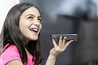 Girl in pink shirt speaking to someone on her smartphone - SBOF00656