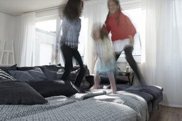 Girls jumping on sofa in living room - SBOF00659